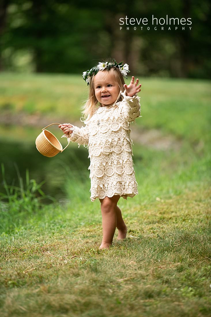 45_Flower girl in white lace and daisy crown throws petals near pond.jpg