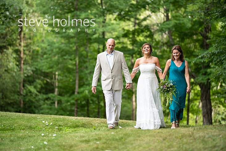 46_Bride walks hand in hand with her parents to outdoor ceremony.jpg