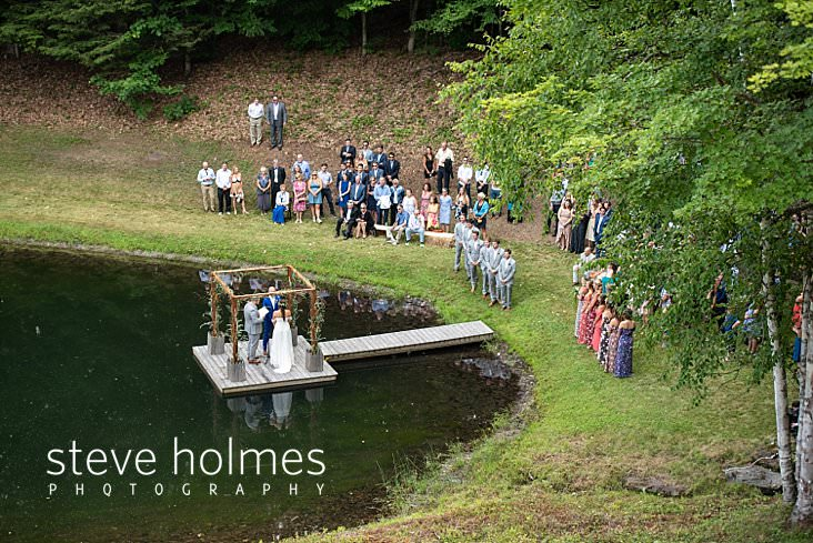 52_Birds eye view of wedding ceremony taking place on a dock on a pond.jpg