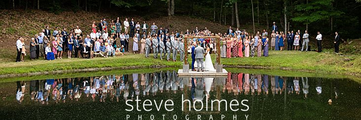 54_Wide shot of wedding ceremony taking place on a dock on a pond.jpg
