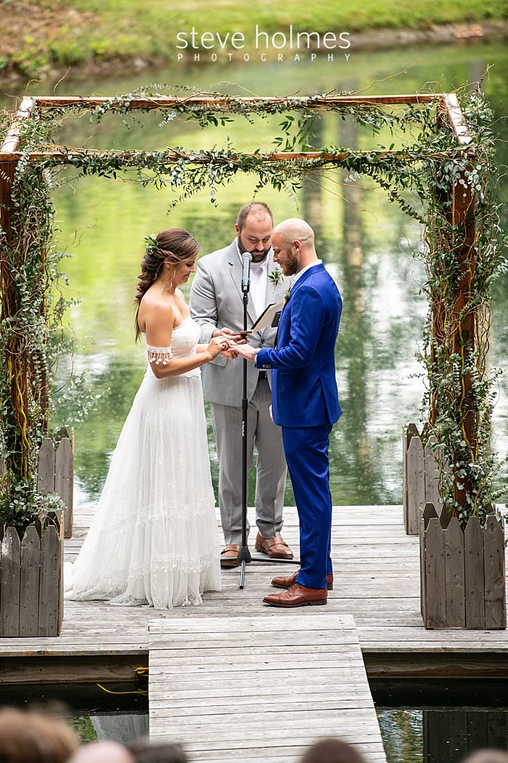 60_Bride puts the ring on her groom's finger in outdoor ceremony on pond.jpg