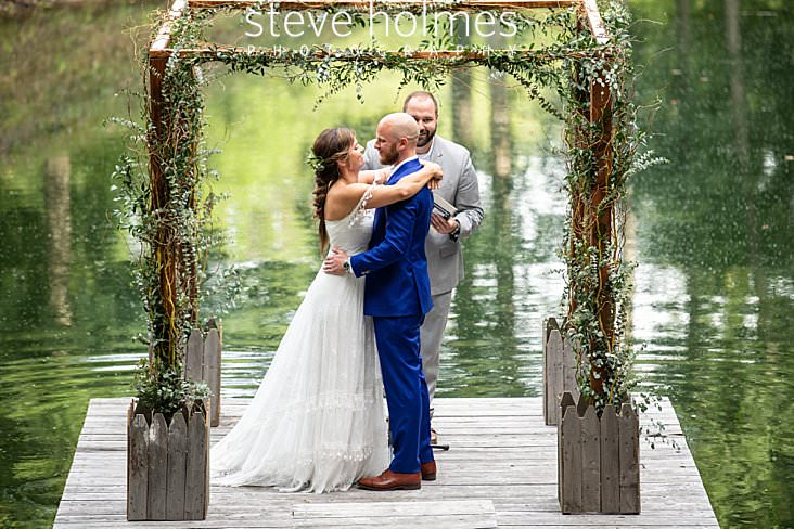 63_Bride and groom hug during ceremony on a dock on a pond.jpg