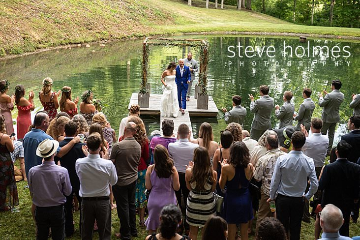 64_Bride and groom walk up dock together after ceremony on pond.jpg