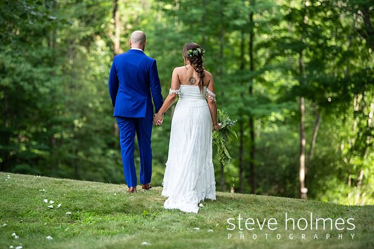 66_Bride and groom walk together in green summer weather.jpg