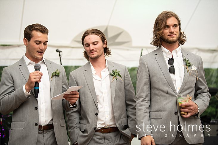 83_Groomsmen read speeches under tent.jpg
