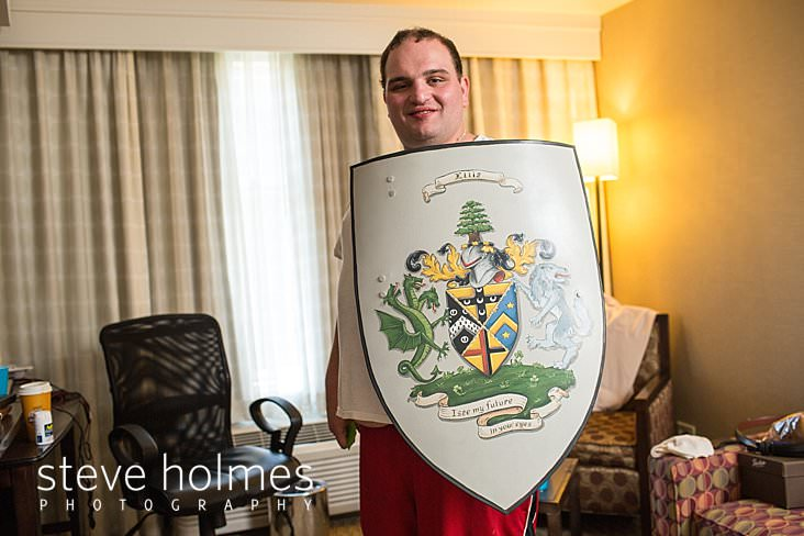 01_Groom holds up his family's shield as he gets ready for wedding.jpg