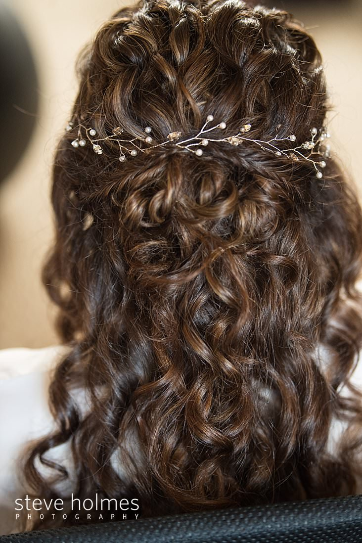 04_Bride has her brown curly hair in a partial updo with a pearl ivy crown woven in.jpg