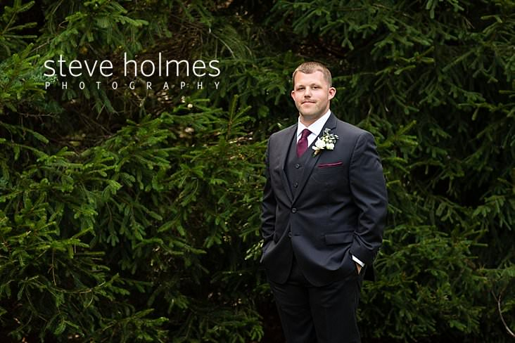 07_Groom stands in his three piece suit with hands in pocket.jpg