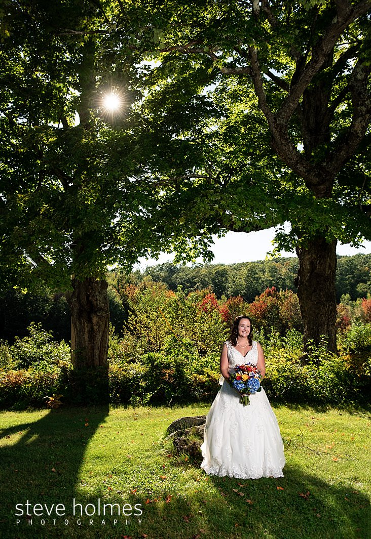 19_Sun shines through maple trees as bride poses with her bouquet.jpg