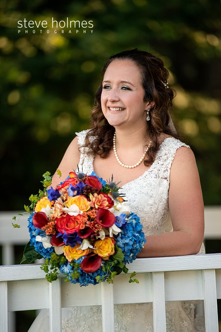 21_Curly haired brunette bride leans on a white railing with her bouquet.jpg