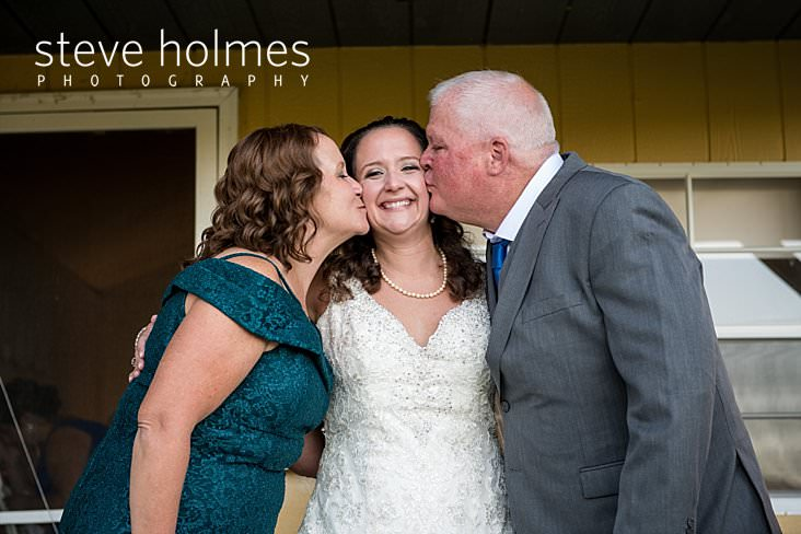 28_Mother and father of the bride kiss her cheeks.jpg