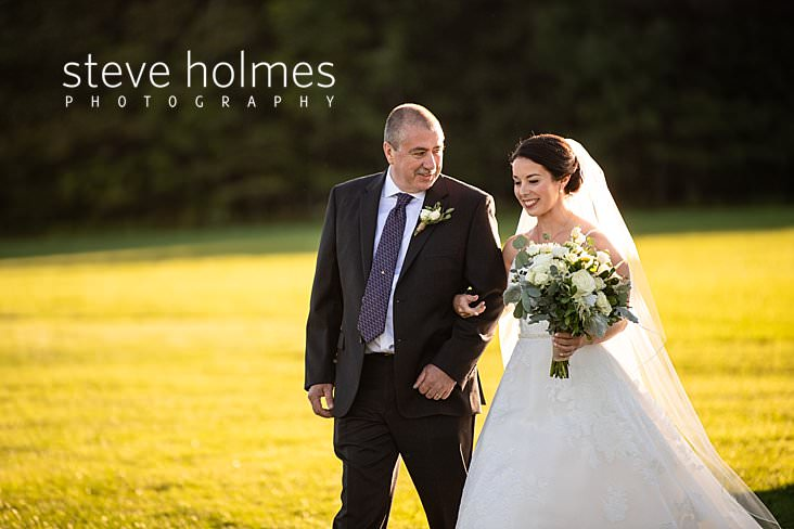 33_Father smiles at his daughter as he walks her down the isle in outdoor wedding ceremony.jpg
