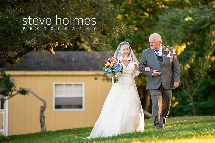 39_Bride holds her father's arm as she walks towards ceremony.jpg