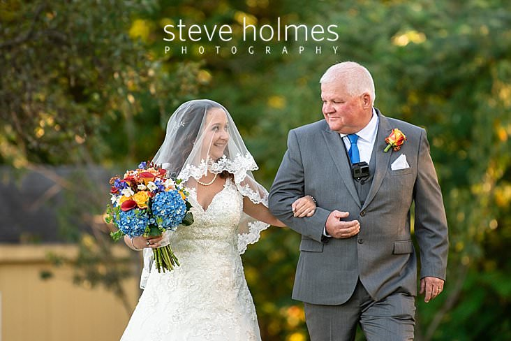 40_Father and bride smile at each other as they walk down isle.jpg