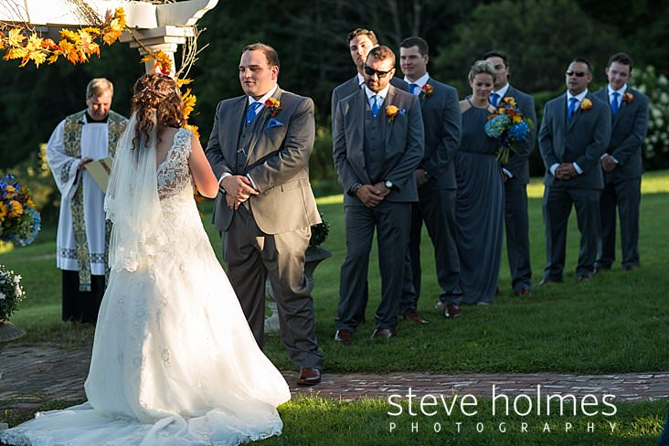 44_Groom recites vows while his bridal party looks on.jpg