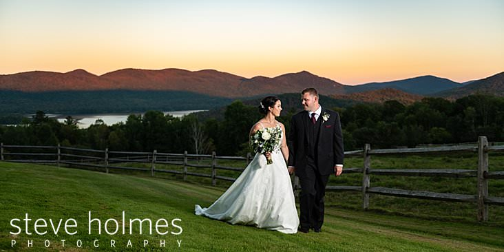 52_Bride and groom walk together at sunset at the Mountain Top Inn and Resort in Vermont.jpg