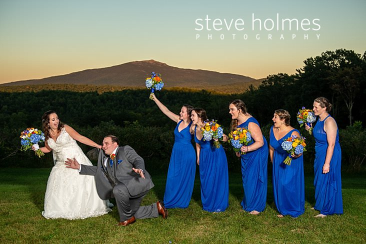 53_Funny portrait of bride dragging groom while bridesmaids laugh.jpg