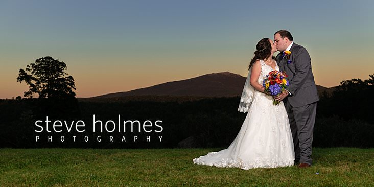 56_Bride and groom kiss at sunset with Mt. Monadnock in background.jpg