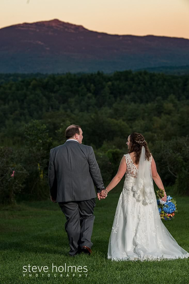 57_Bride and groom walk together at sunset towards Mt. Monadnock.jpg
