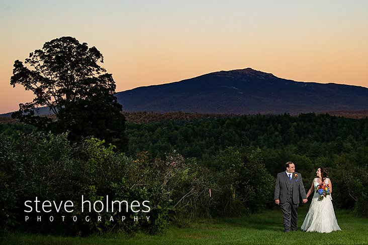 58_Bride and groom smile at each other and walk hand in hand with Mt. Monadnock in backdrop.jpg