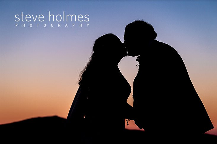 60_Silhouette of bride and groom kissing at sunset.jpg