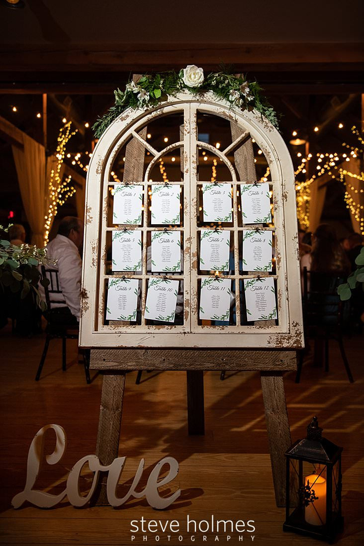 64_Wedding reception table assignment in old arch window frame.jpg
