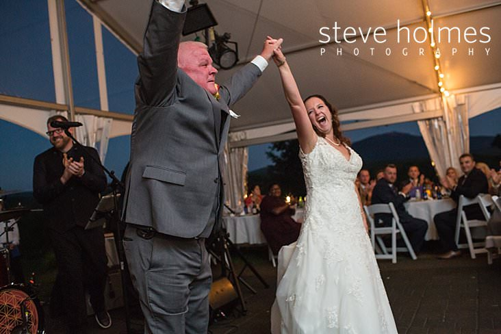 66_Father and bride hold their hands in the air and laugh.jpg