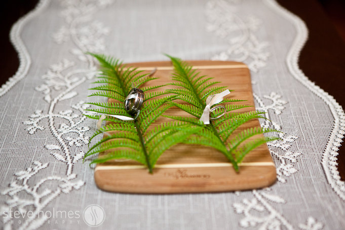 Wedding rings tied to ferns on a bamboo board.