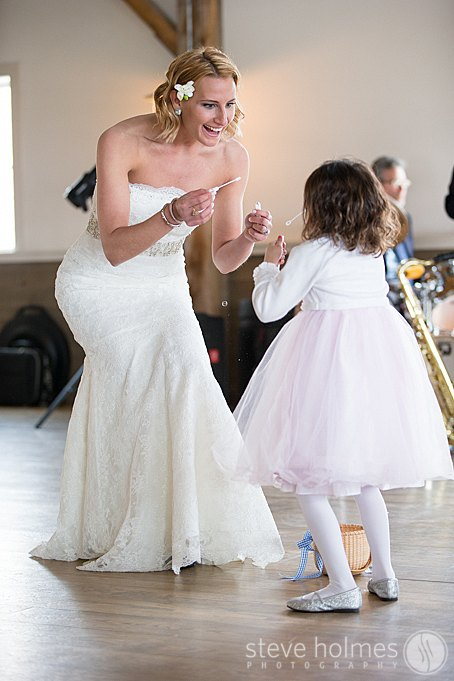 The bride shared a special moment with her flower girl blowing bubbles.