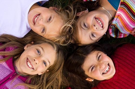 Portrait of four children lying down.