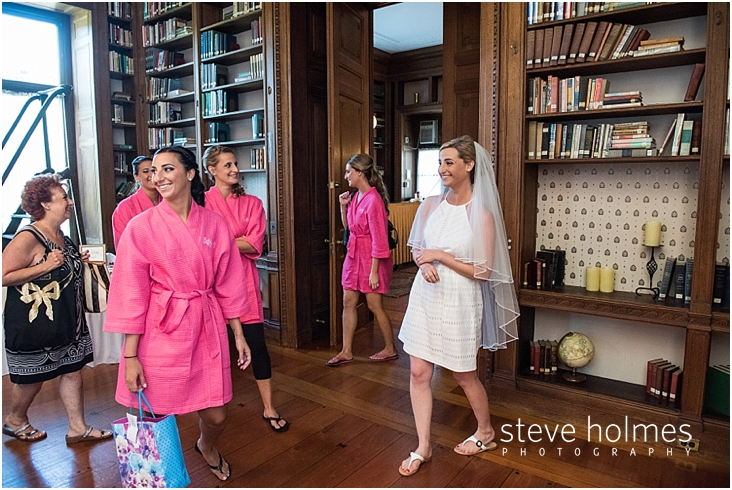 06_bridesmaids-wear-pink-robes-bride-wears-white-dress-as-they-get-ready