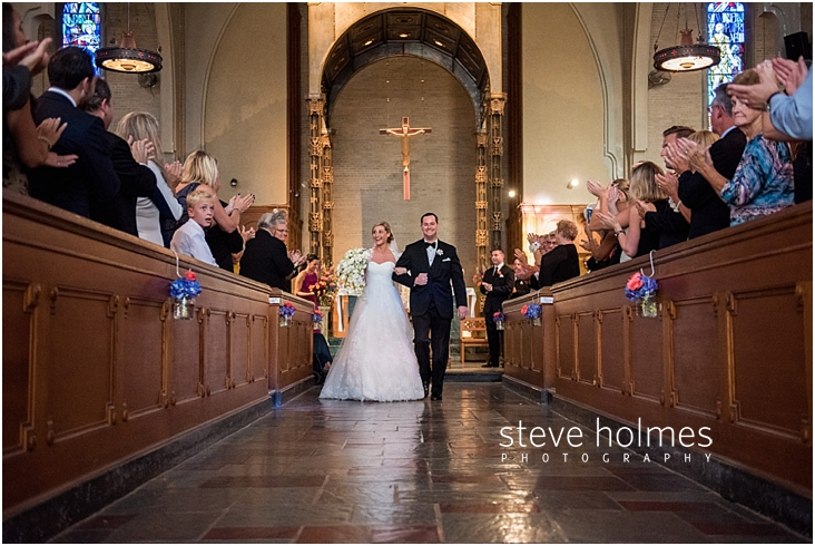 42_bride-and-groom-smile-as-they-walk-down-aisle-together