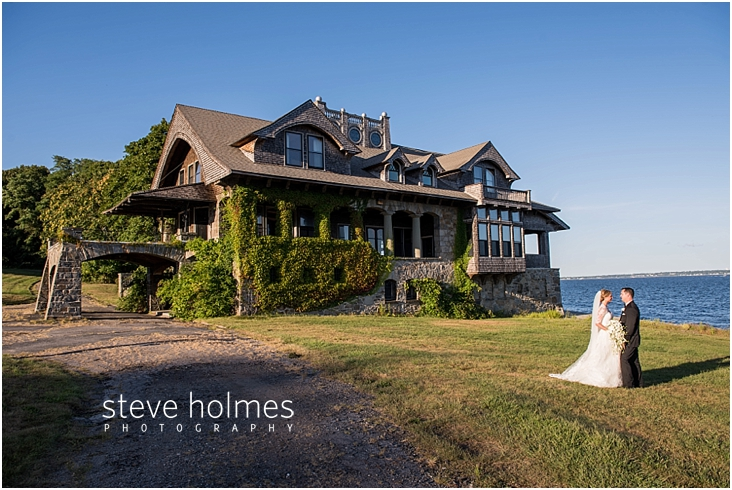49_bride-and-groom-stand-by-boat-house-along-shore