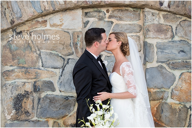 50_bride-and-groom-kiss-by-stone-wall