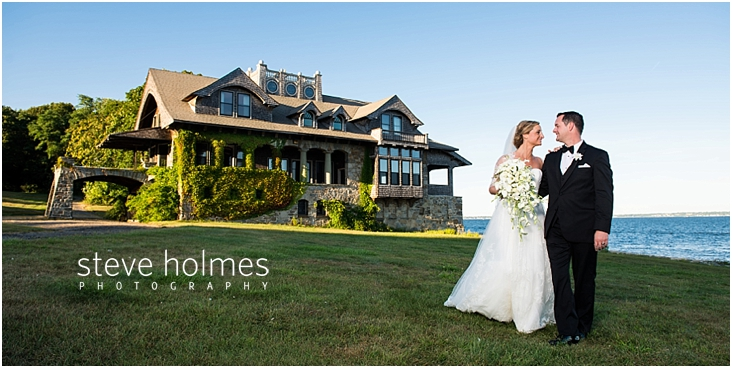 53_bride-and-groom-stand-by-boat-house-along-shore