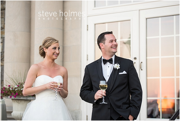 60_bride-and-groom-smile-while-holding-wine-glasses