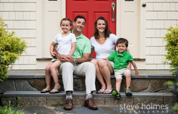 A family of four poses on their front stoop
