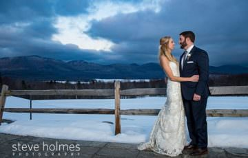 Bride and groom smile at each other on patio overlooking winter mountain landscape