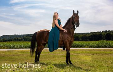 Young woman wearing long blue dress poses on her horse in front of a corn field