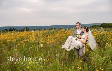 Groom carries bride through a field of wildflowers