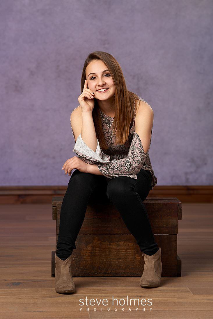 01_Brunette teen sits on a wooden box for studio portrait.jpg