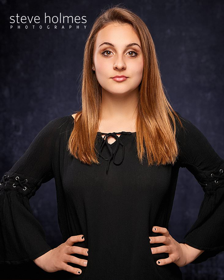 02_Young woman wearing black long sleeve blouse looks directly at the camera for studio senior portrait.jpg