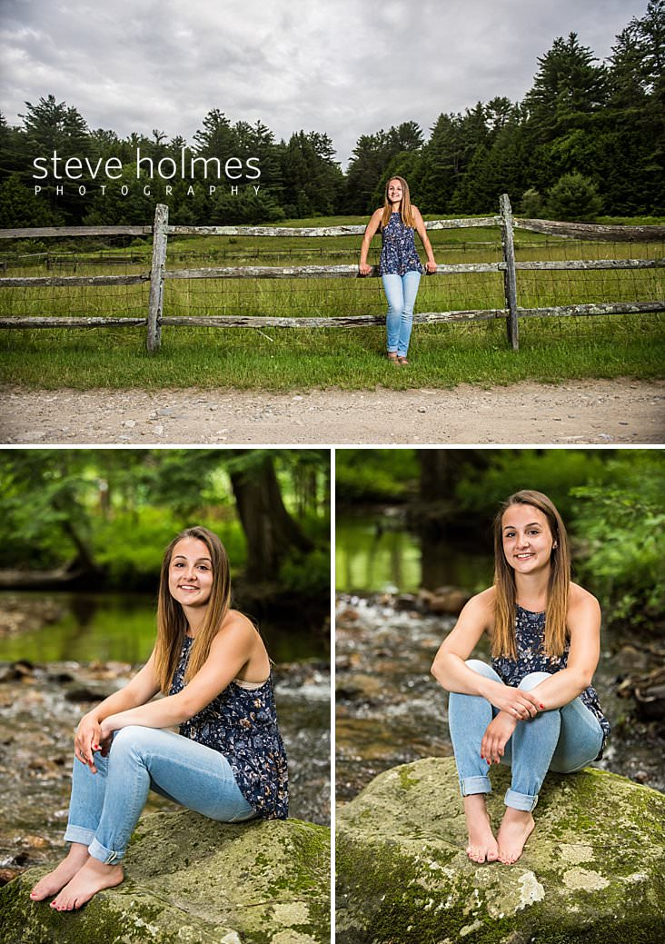 04_Young woman in jeans and flowered blouse leans against wooden fence with country field and forests behind her.jpg
