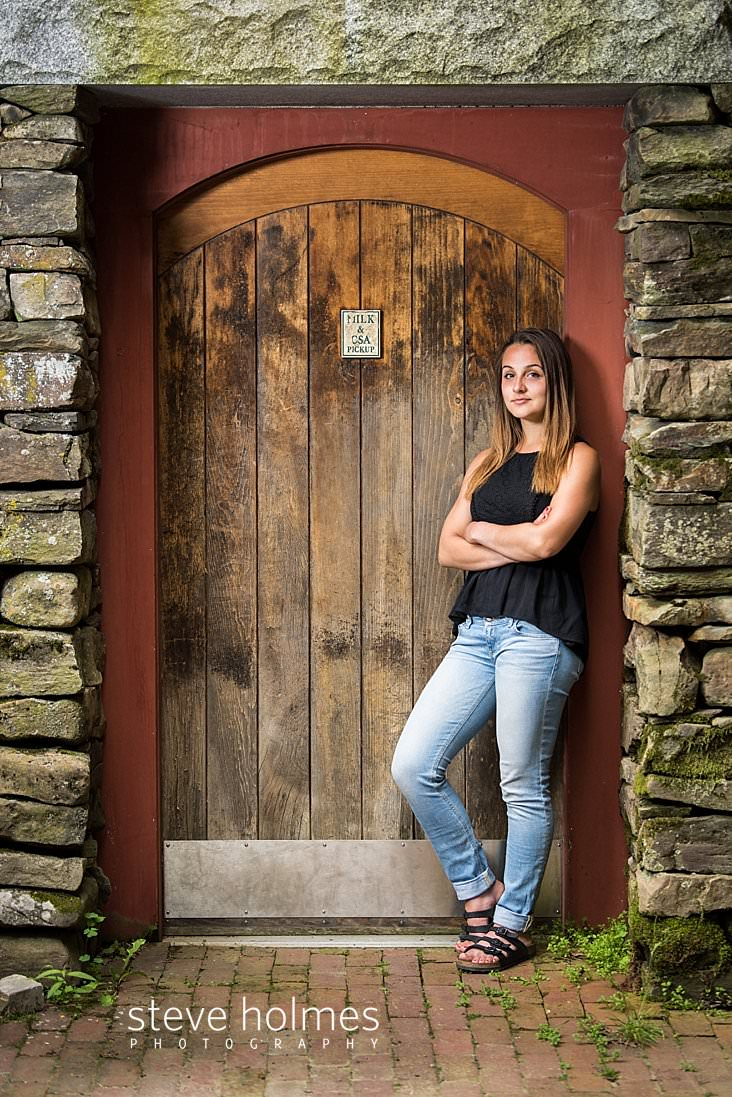 10_Brunette young woman stands in arch of wooden door with arms crossed for senior portrait.jpg