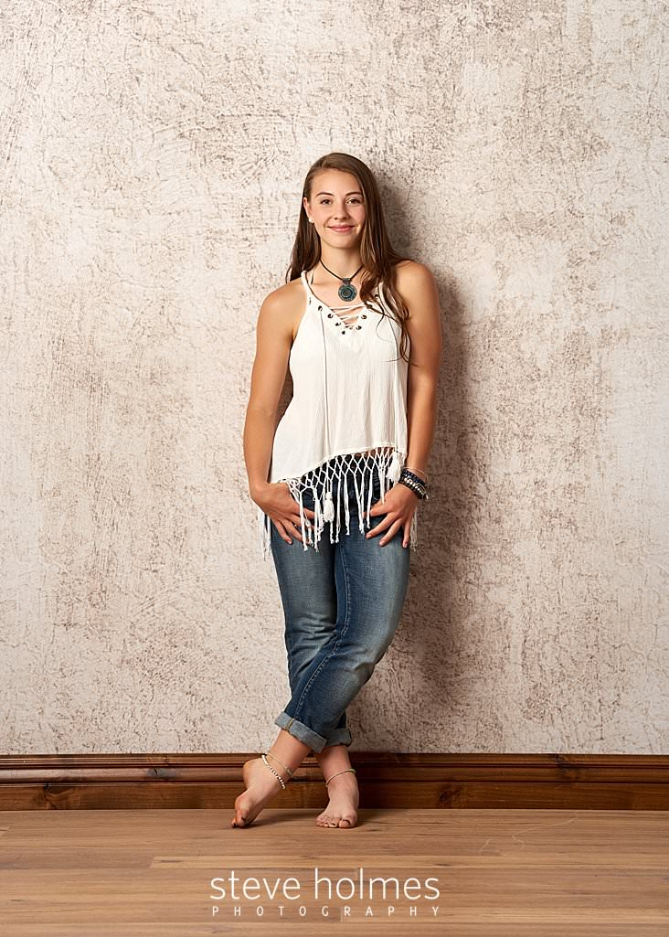 01_Teen girl poses barefoot for studio senior portrait in jeans and a white tank top.jpg