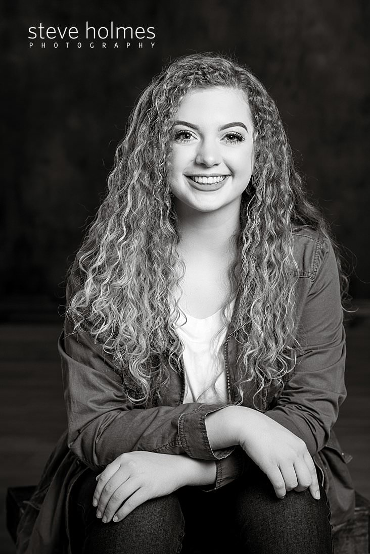 03_Black and white studio portrait of young woman with curly hair wearing jacket and jeans.jpg