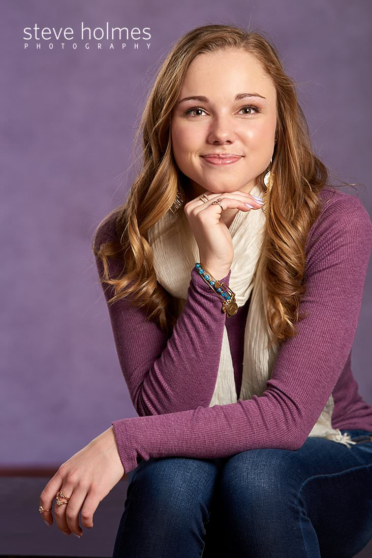 03_Young woman in purple long sleeve, jeans and a scarf sits with hand on chin for studio senior portrait.jpg