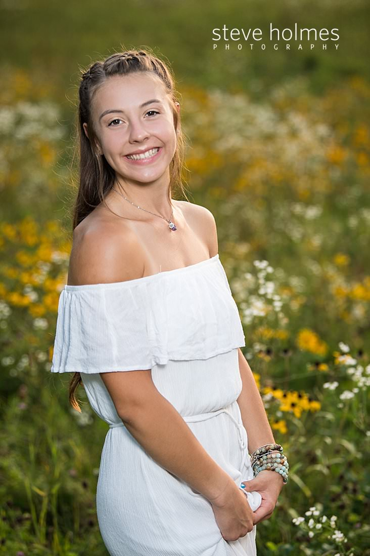 04_Young woman wearing white dress stands in field of wildflowers for senior portrait.jpg