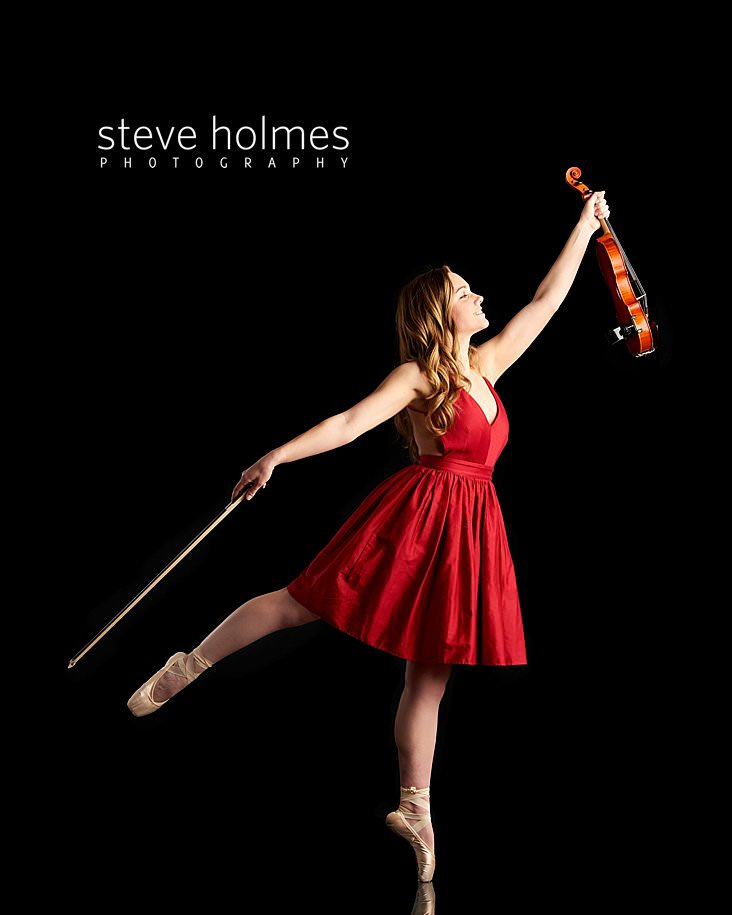 07_Young woman wearing red dress and ballet slippers dances with violin for studio senior portrait.jpg