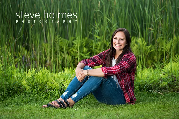 09_Teenaged girl with brown hair sits on the grass in front of a pond for senior portrait.jpg